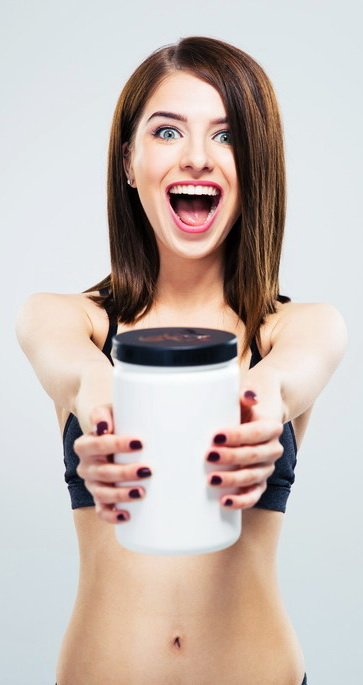 Cheerful smiling sporty woman with jar of protein over gray background and looking at camera